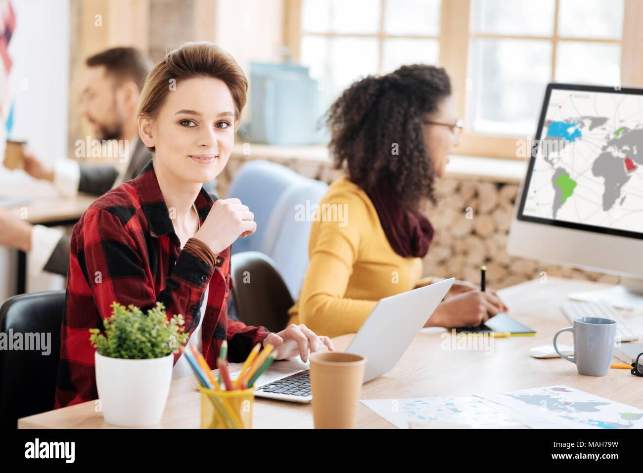 Fröhliche blonde Frau an ihrem Laptop Stockfoto