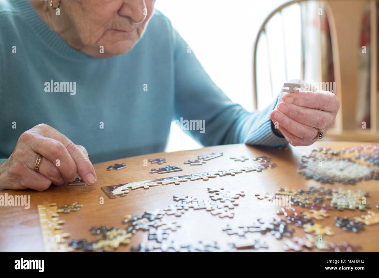Nahaufnahme der älteren Frau entspannend mit Puzzle zu Hause Stockbild