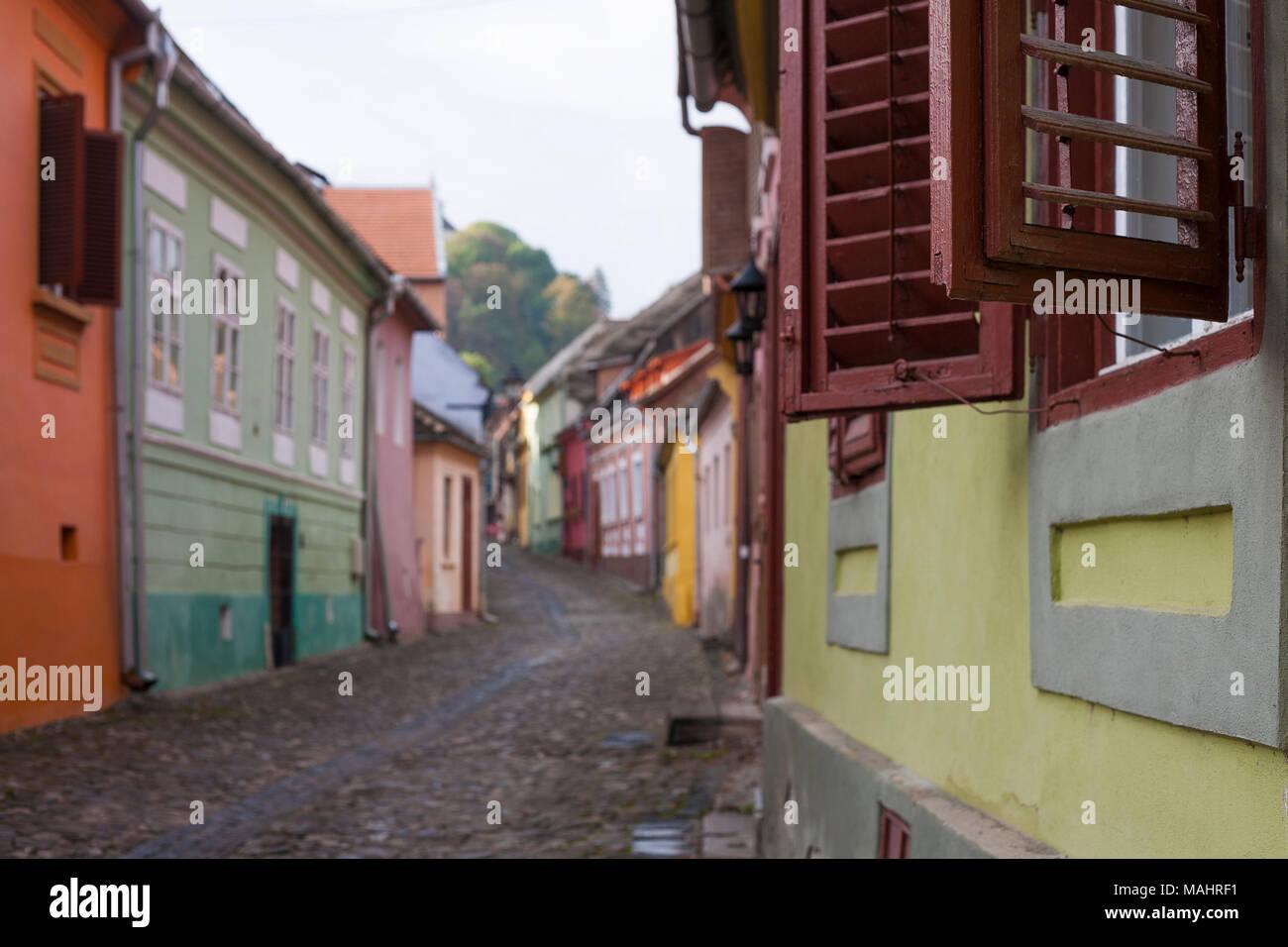 Gepflasterten Straßen führen vorbei an bunten alten Häusern zur Zitadelle in Sighisoara, Rumänien Stockfoto