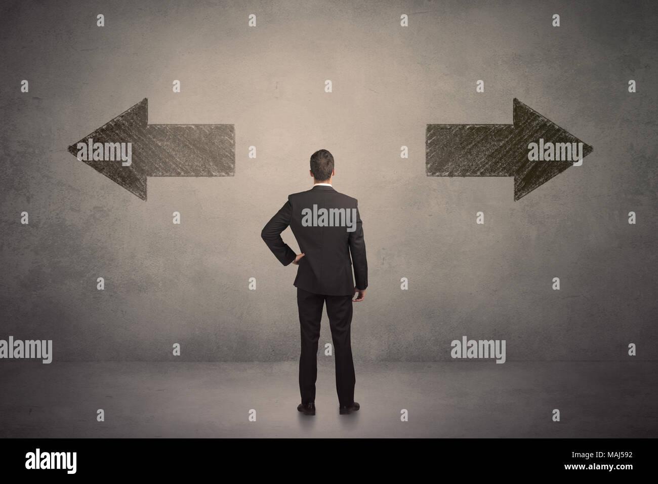 Business Mann treffen sie eine Entscheidung, während man vor zwei grungy Pfeile auf Wand Konzept Stockbild