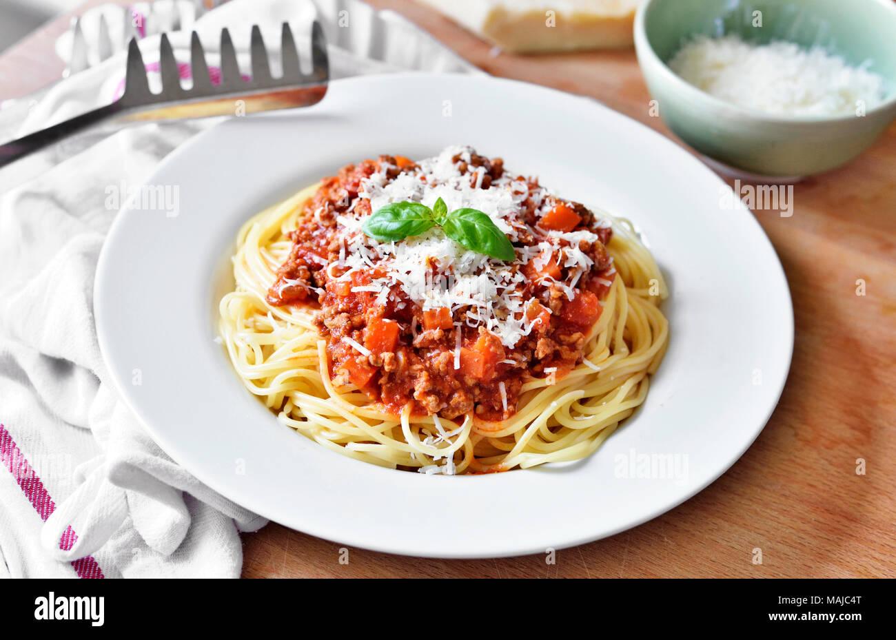 Leckere Pasta essen, Spaghetti Bolognese auf einem weißen Teller. Nudelgericht, traditionelle italienische Küche mit Parmesan Käse, Hackfleisch und Basil leaf. Stockbild