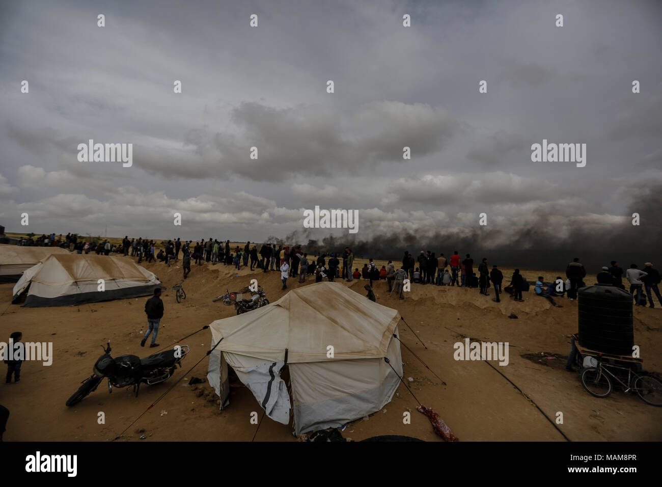 Palästinensische Demonstranten ansehen Rauchwolken, wie sie von verbrannten Reifen steigen, die israelischen Truppen abzulenken, während Auseinandersetzungen entlang der Grenzen zwischen Israel und Gaza, östlich von Khan Yunis, im südlichen Gazastreifen, 03. April 2018. Foto: Mohammed Talatene/dpa Stockfoto