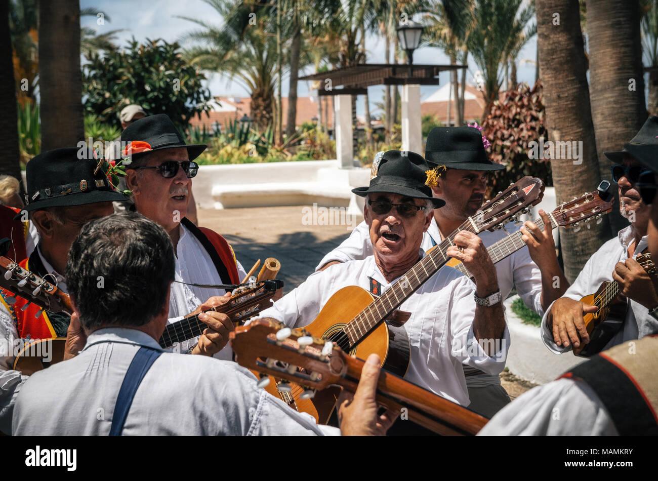 Puerto de la Cruz, Teneriffa, Kanarische Inseln - 30. Mai 2017: Kanaren Menschen in traditionellen Kleidern bekleidet Spaziergang entlang der Straße, Zeichen und Gitarre spielen Stockbild