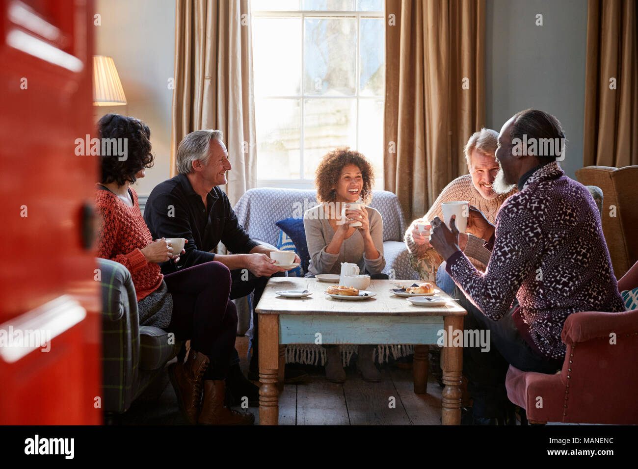 Gruppe der mittleren Alter Freunde zu treffen um den Tisch im Café Stockbild