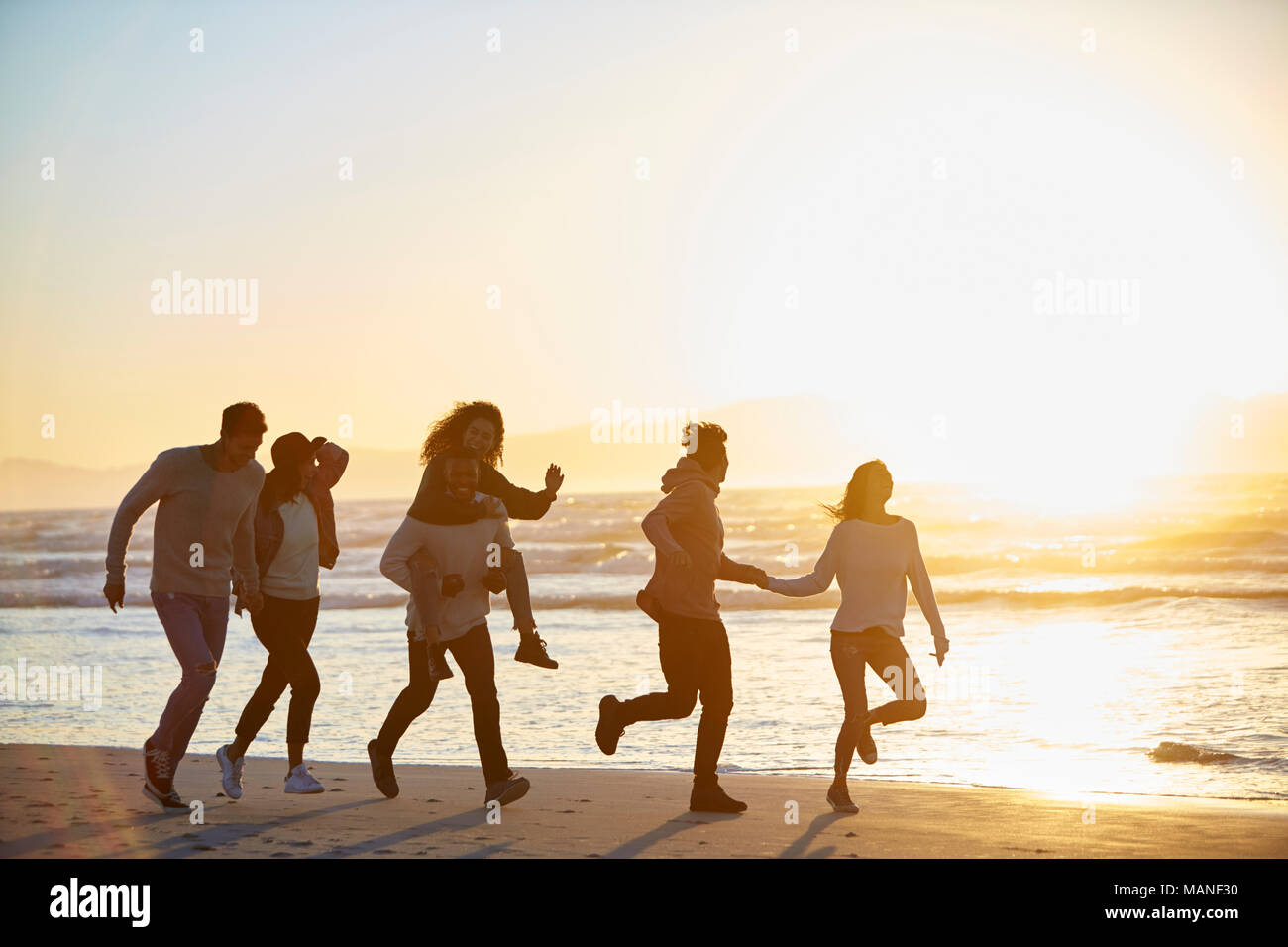 Silhouette von Freunden Spaß entlang Winter Strand Stockbild