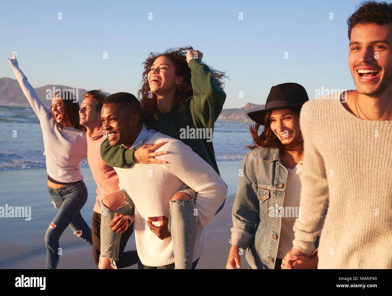 Gruppe von Freunden Spaß entlang Winter Beach Zusammen läuft Stockbild