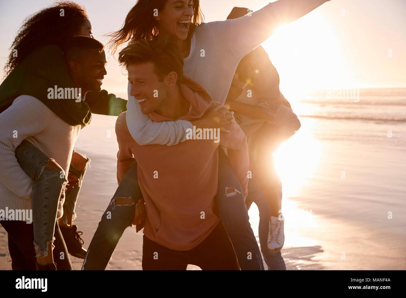 Eine Gruppe von Freunden mit Piggyback Rennen auf Winter Beach zusammen Stockbild