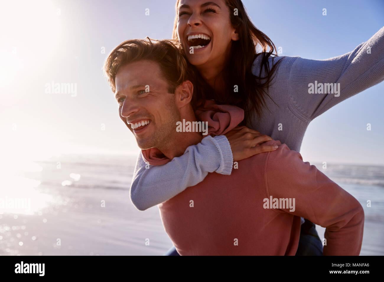 Mann, Frau, Huckepack auf Winter Urlaub am Strand Stockbild