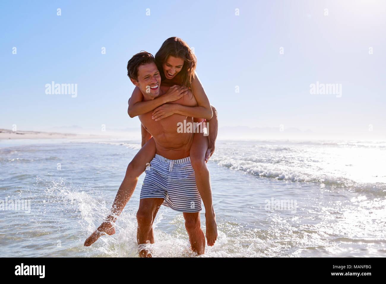 Mann, Frau, Huckepack auf Sommer Strand Ferienhäuser Stockbild