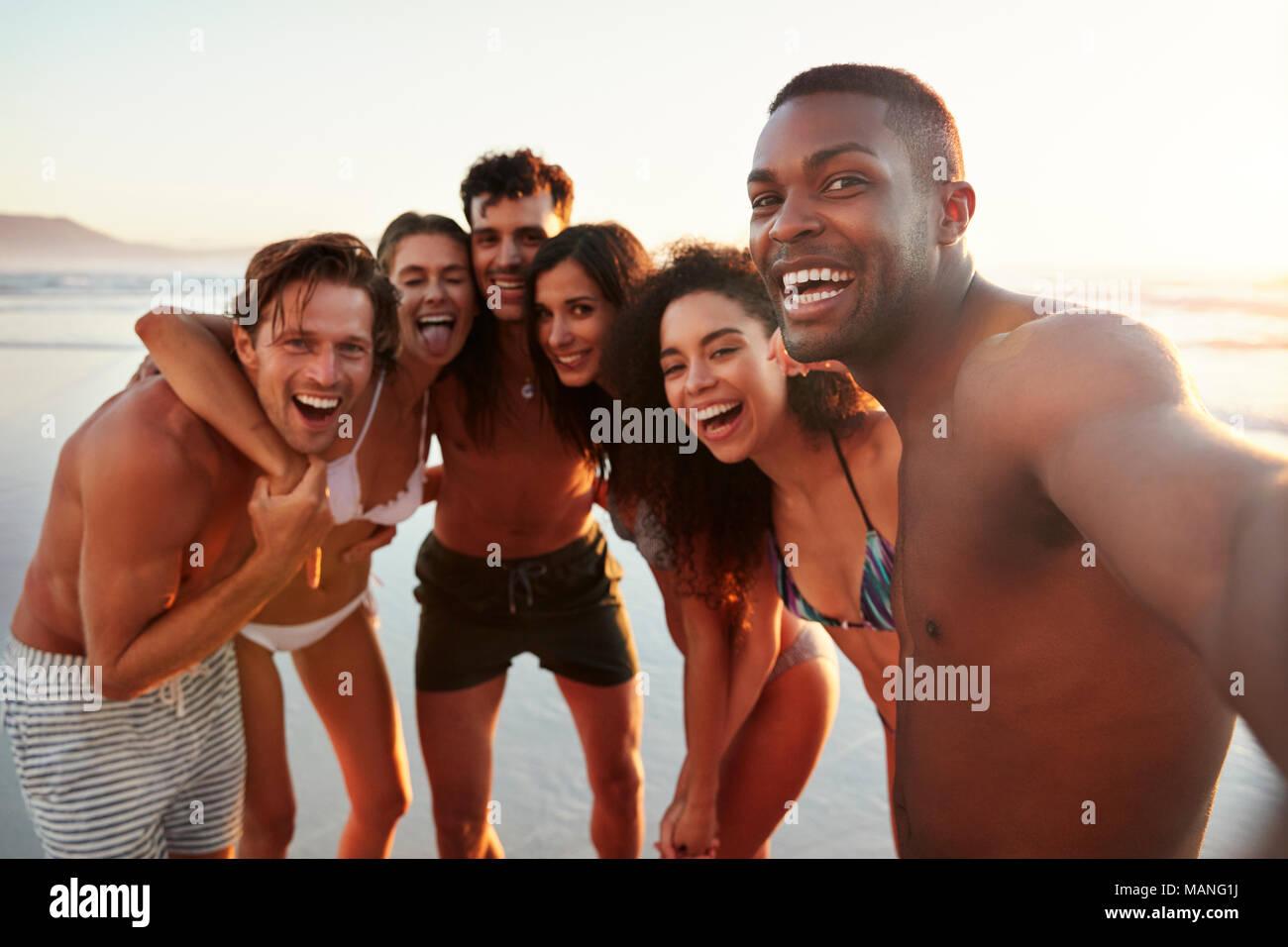 Gruppe von Freunden Posieren für Selfie zusammen am Strand Ferienhäuser Stockbild