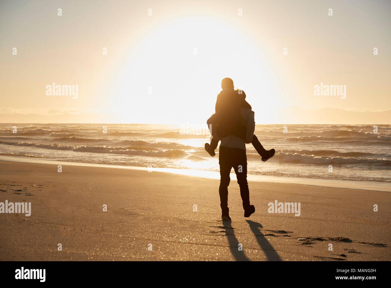 Silhouette von Vater und Sohn Huckepack auf Winter Strand Stockbild