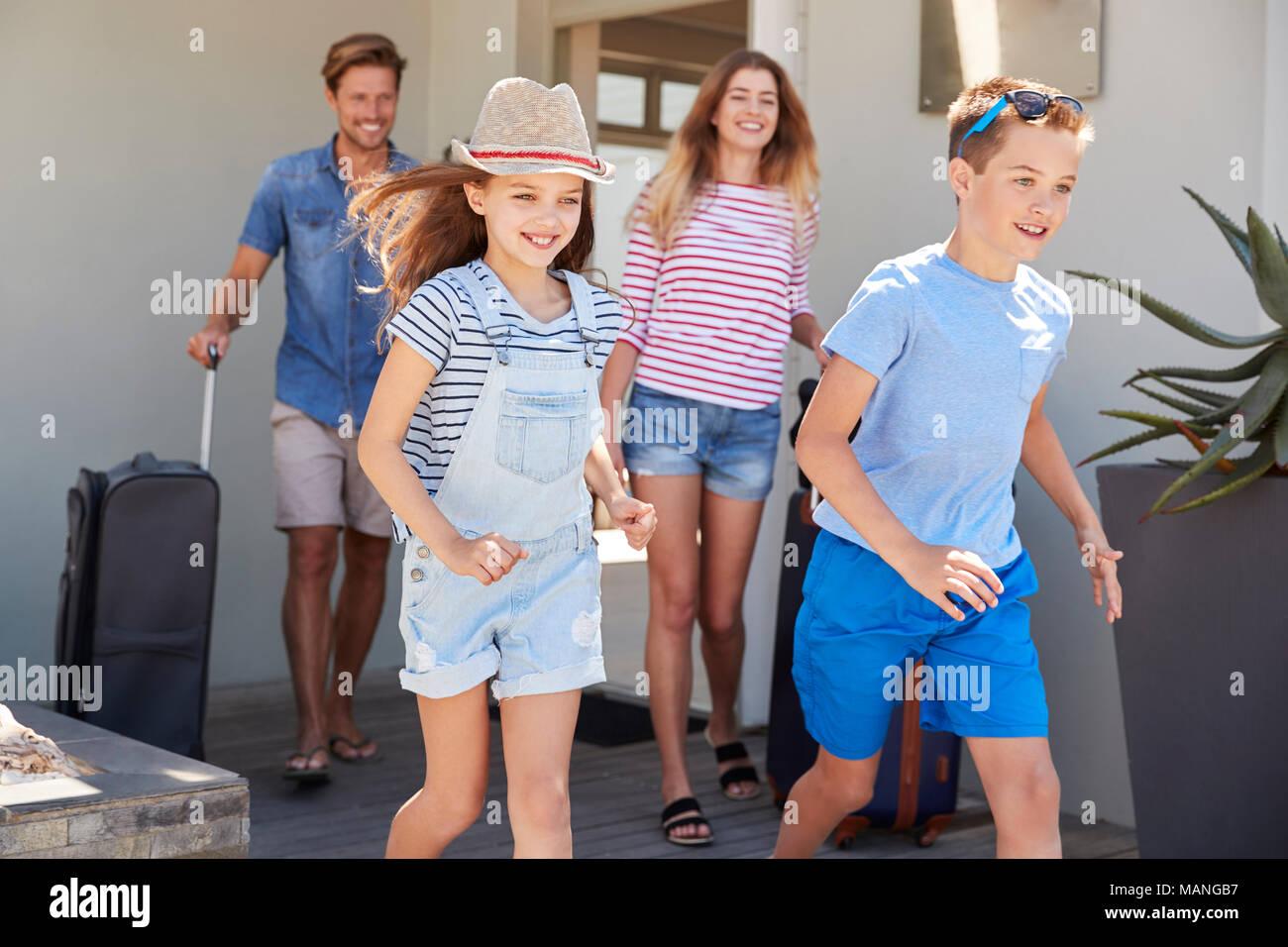 Familie mit Gepäck verlassen Haus für Ferienhäuser Stockbild