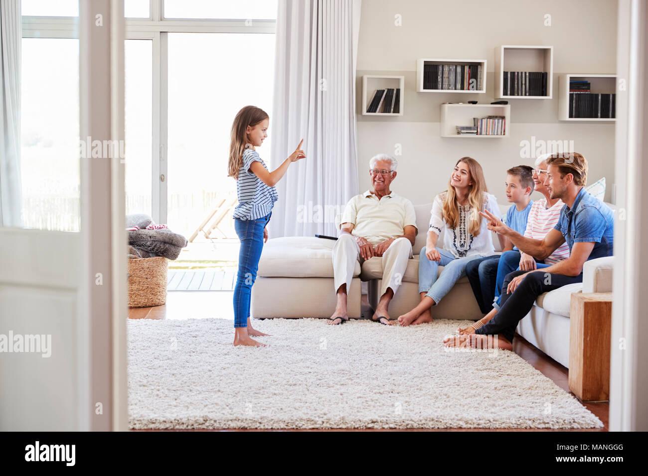 Multi-Generation Familie sitzt auf dem Sofa zu Hause spielt Scharaden Stockbild