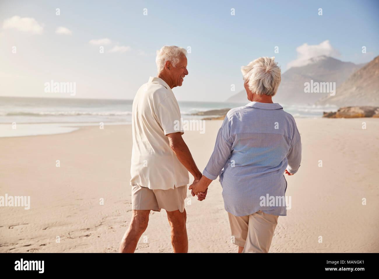 Ansicht der Rückseite des Senior Paar am Strand entlang zu laufen Hand in Hand Stockfoto