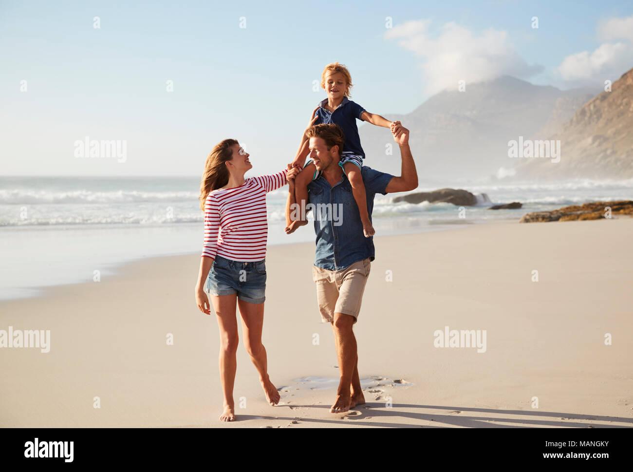 Eltern mit Sohn auf den Schultern am Strand Ferienhäuser Stockbild