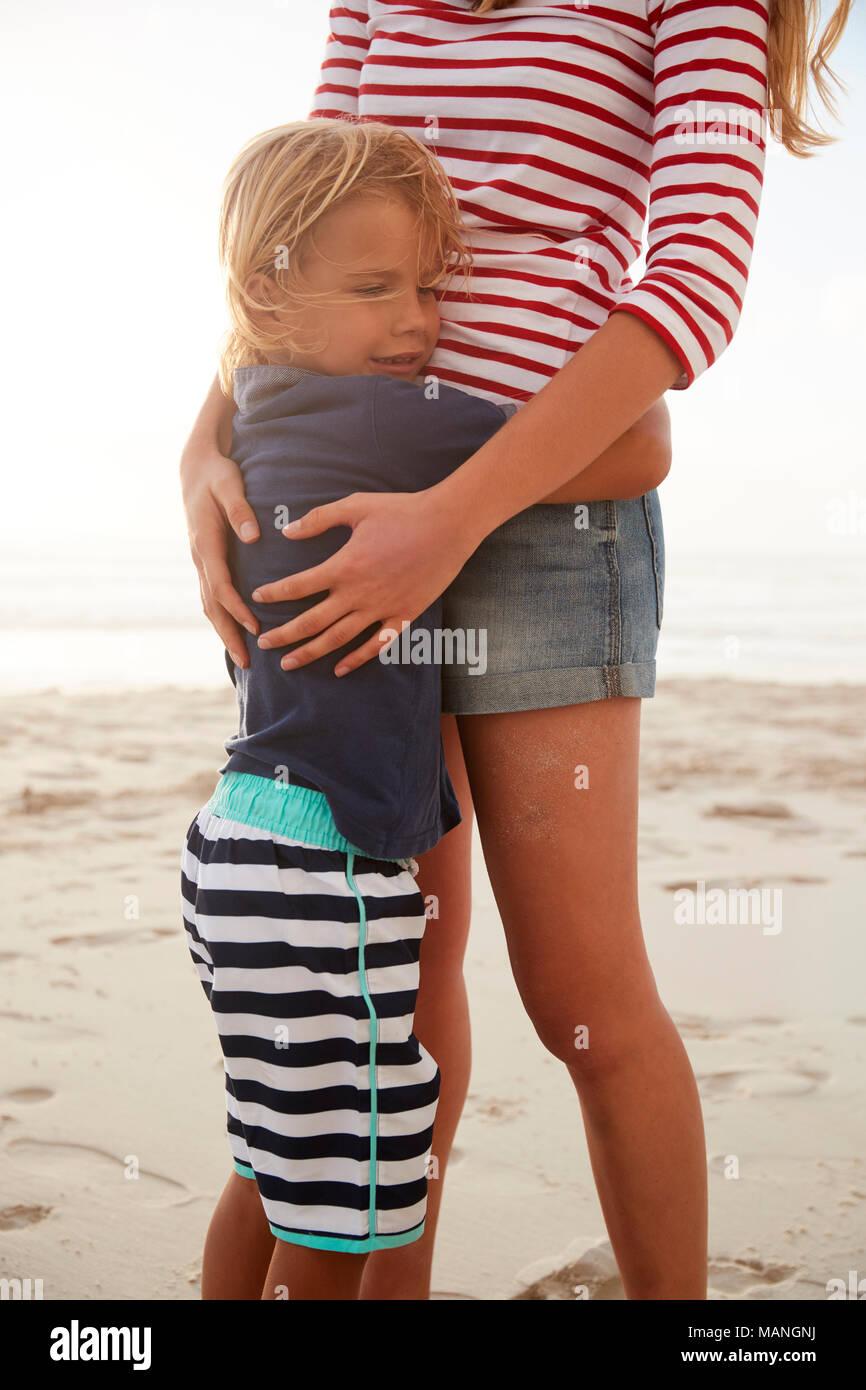 Nahaufnahme der Mutter umarmt Sohn auf Sommer Strand Ferienhäuser Stockbild