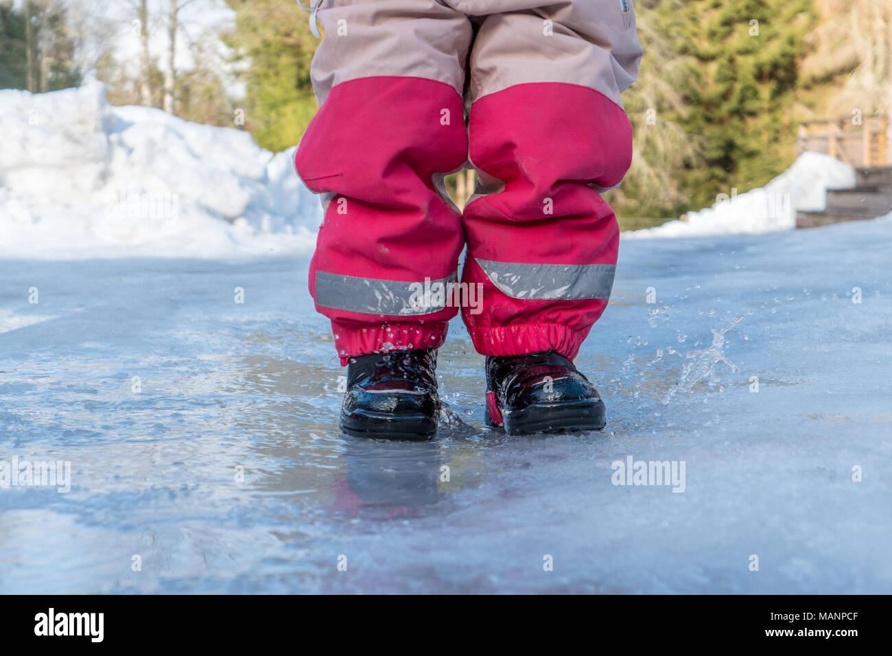 Kleines Kind im Wasser springen mit Gummistiefeln auf Stockbild