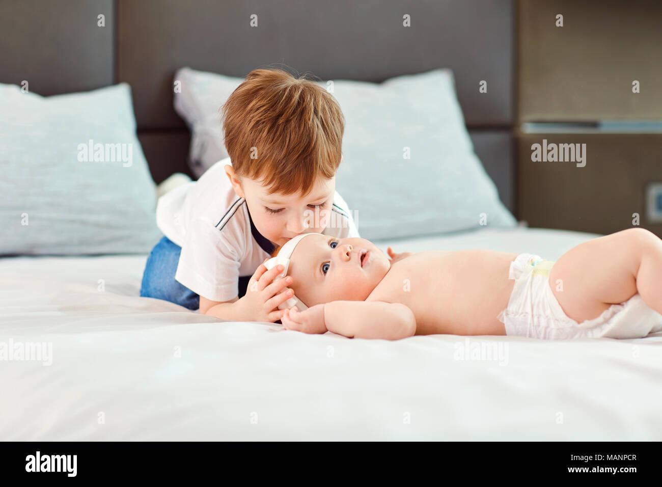 Ein kleiner Junge, der mit seiner kleinen Schwester Umarmungen und Küsse auf dem Bett. Stockbild