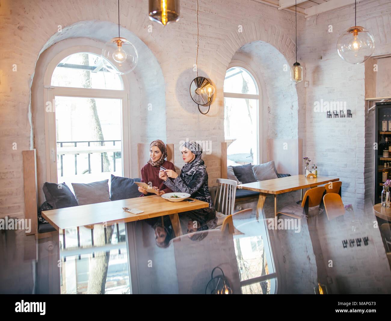 Zwei Business Partner mittels Tablet vor ihren Coffee Shop Stockbild