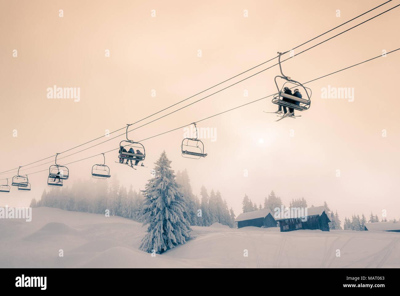 Skifahrer und Snowboarder unterwegs auf einem Sessellift in Morzine Skigebiet in Frankreich. Split getönten Farben Behandlung. Stockbild