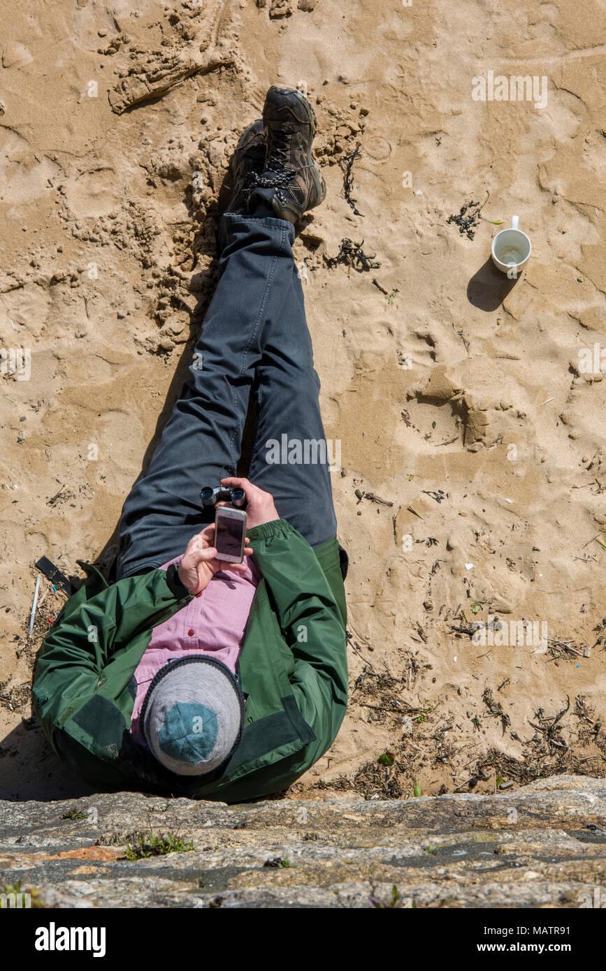 Ein Mann sitzt auf einem Sandstrand lehnte sich gegen die Hafenmauer mit einem Handy oder einem tragbaren Gerät zu kommunizieren. Nehmen es einfach am Strand. Stockbild