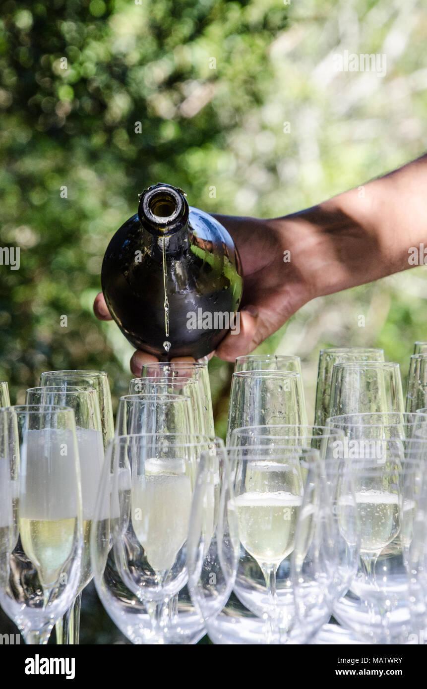 Mans hand gießt Sekt in Gläser im freien Fall. Feiern mit Champagner auf sonnigen Tag. Stockbild