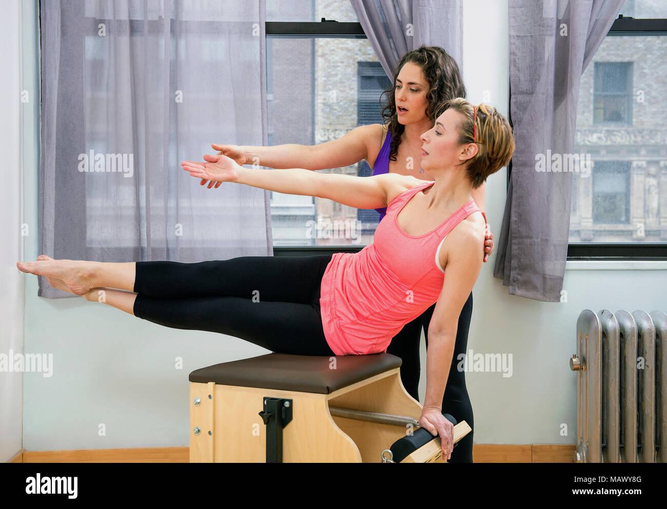 Eine Frau lehre Pilates an einen Studenten. Stockbild