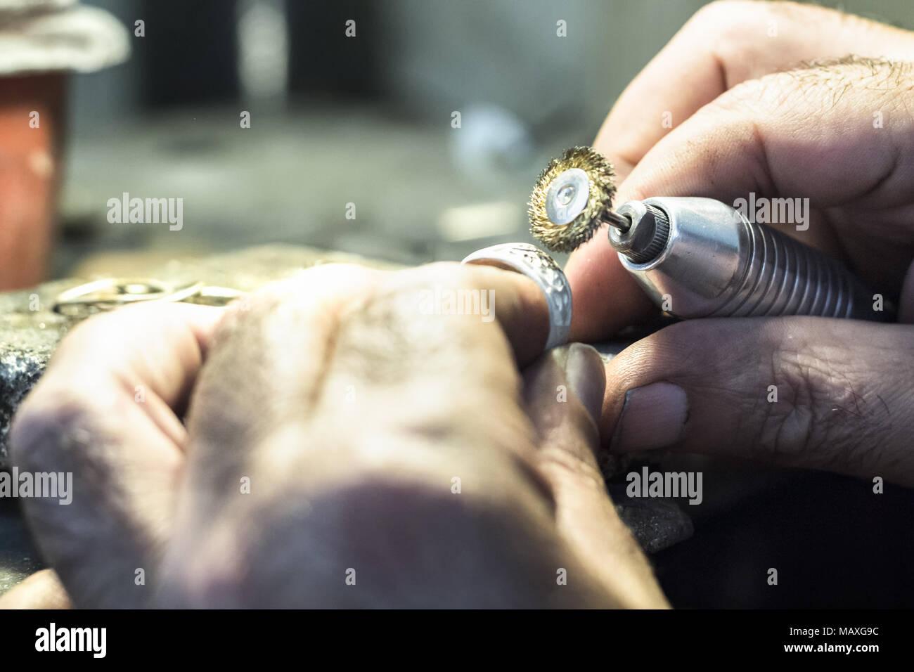 Männliche Juwelier polieren ein silberner Ring mit einem kupferdraht ...