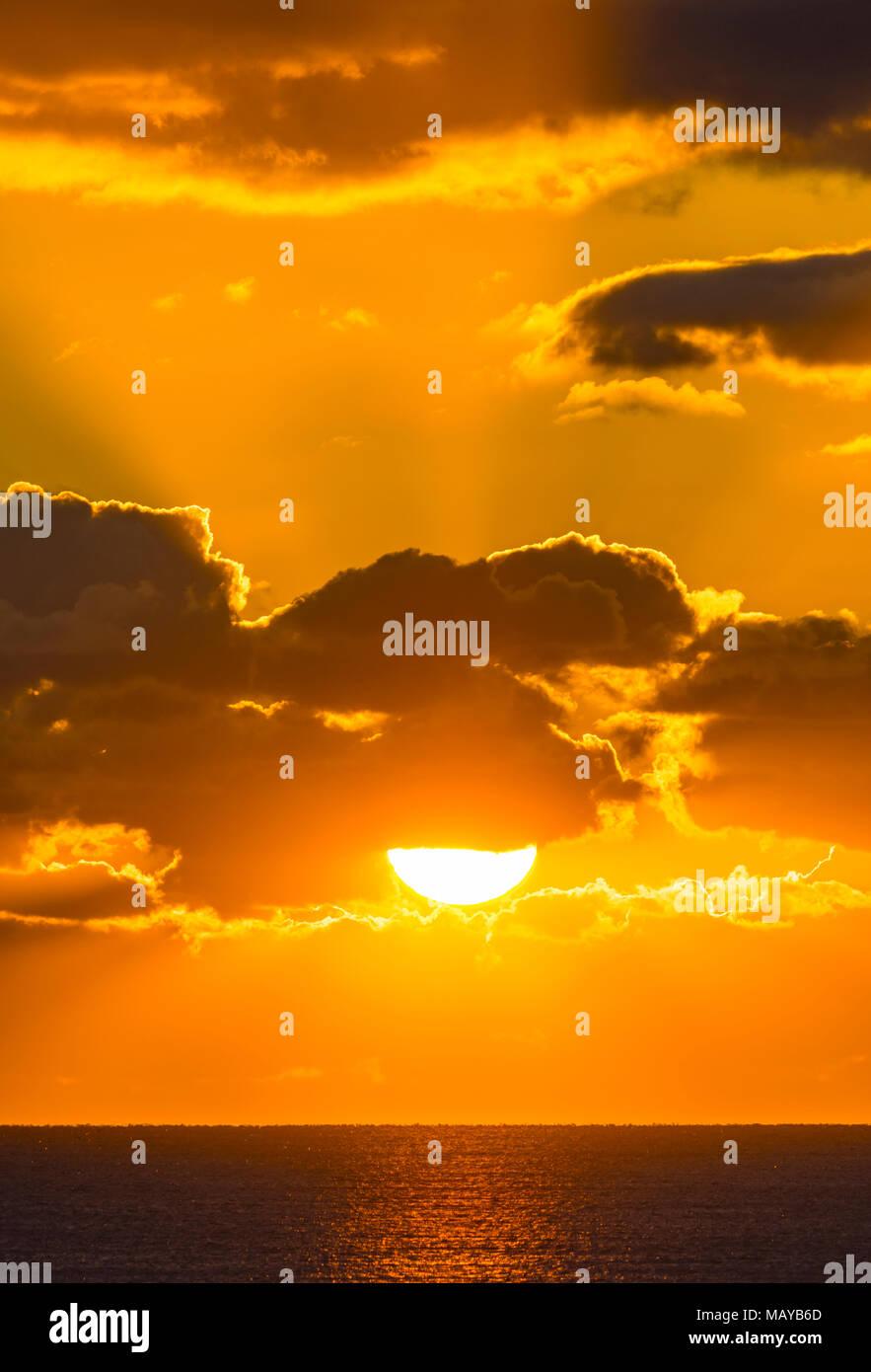 Sonnenuntergang über dem Meer mit Strahlen von der Sonne durch die Wolken wie die Wolke deckt teilweise die niedrige Sonne. Stockbild