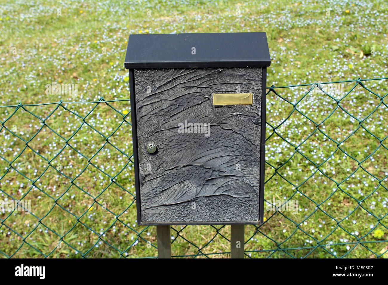 Schwarz geschnitzt Mailbox montiert auf grüner Draht Zaun mit ...