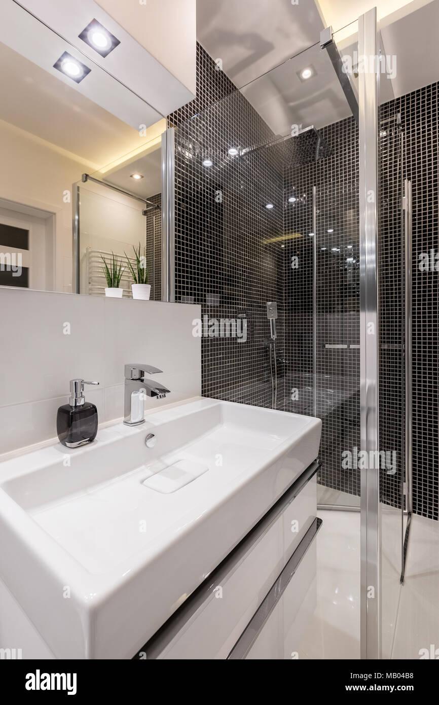 Badezimmer mit weißen Waschbecken, Spiegel und schwarz ...