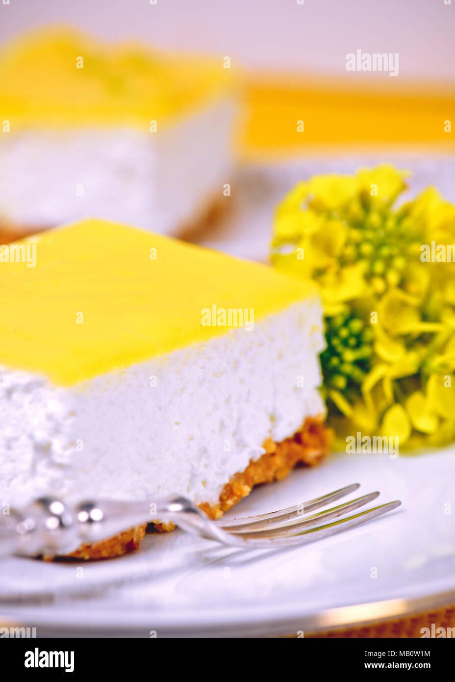 Scheibe der Zitrone Mousse auf einem weißen mit einem silbernen Gabel und gelbe Blumen bokeh Hintergrund Anzeige Kopie Raum Stockbild