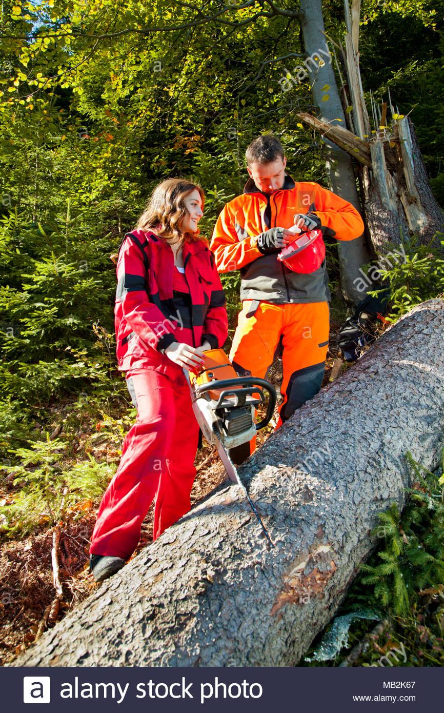 Extrem Holzfäller und junge Frau mit Motorsäge einstellen Helme. Sie hat NA66