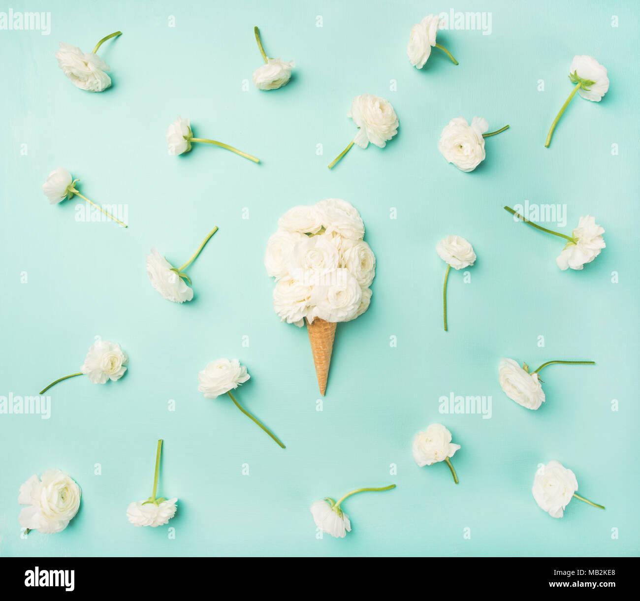 Waffel Kegel mit weißen buttercup Blumen über blauer Hintergrund Stockbild