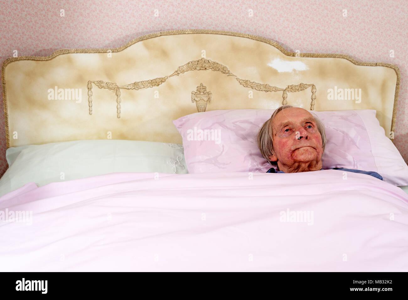 Alter Rentner wach im Bett Stockbild