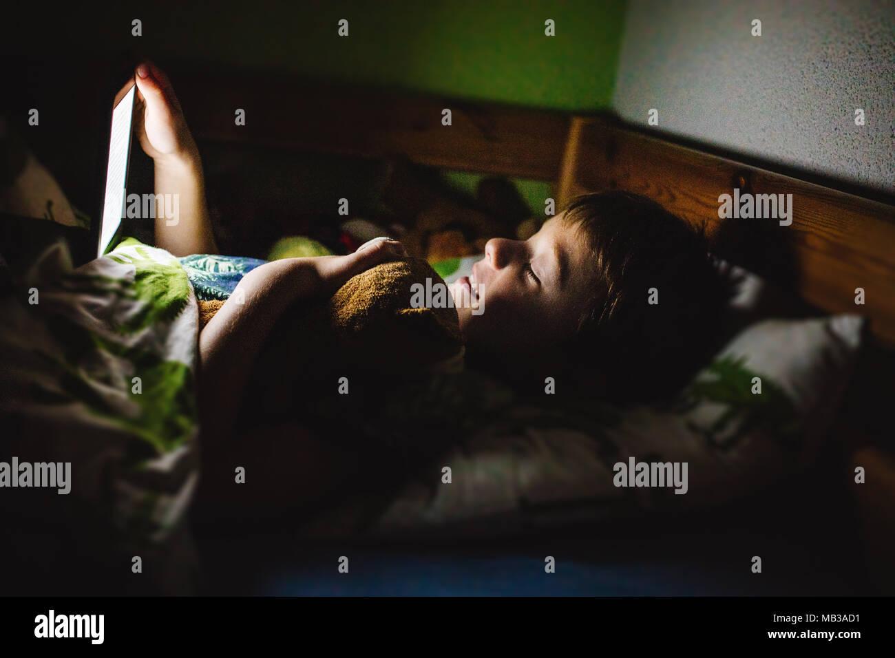 Junge lesen ein elektronisches Buch mit integriertem Licht im Bett vor dem Einschlafen. Tägliche Technologie in der Kinder leben. Dunkler Hintergrund, wenig Licht. Stockbild