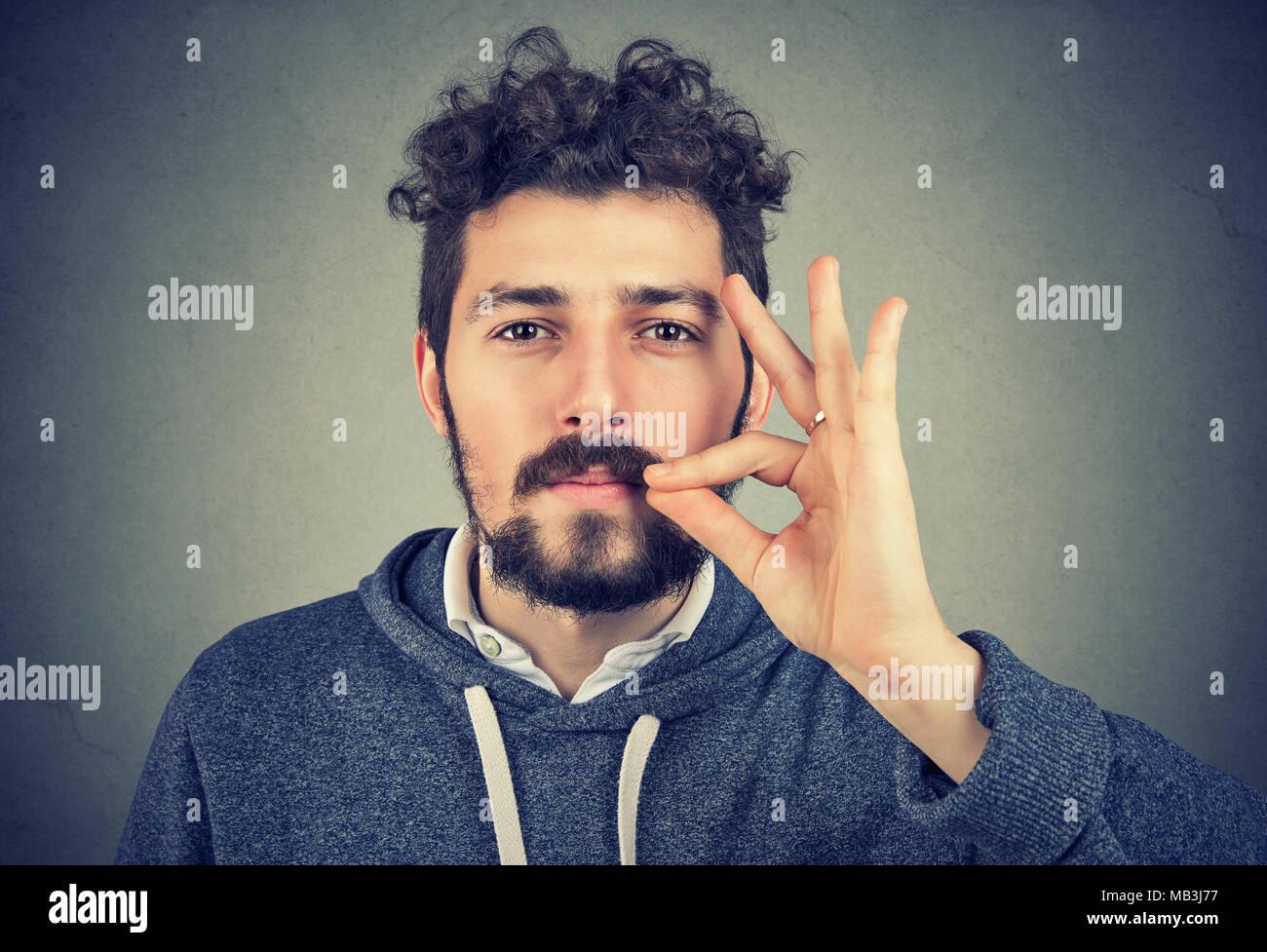 Zuversichtlich ernster Mann zippen Mund halten vertrauliche Daten Kamera schaut. Stockbild