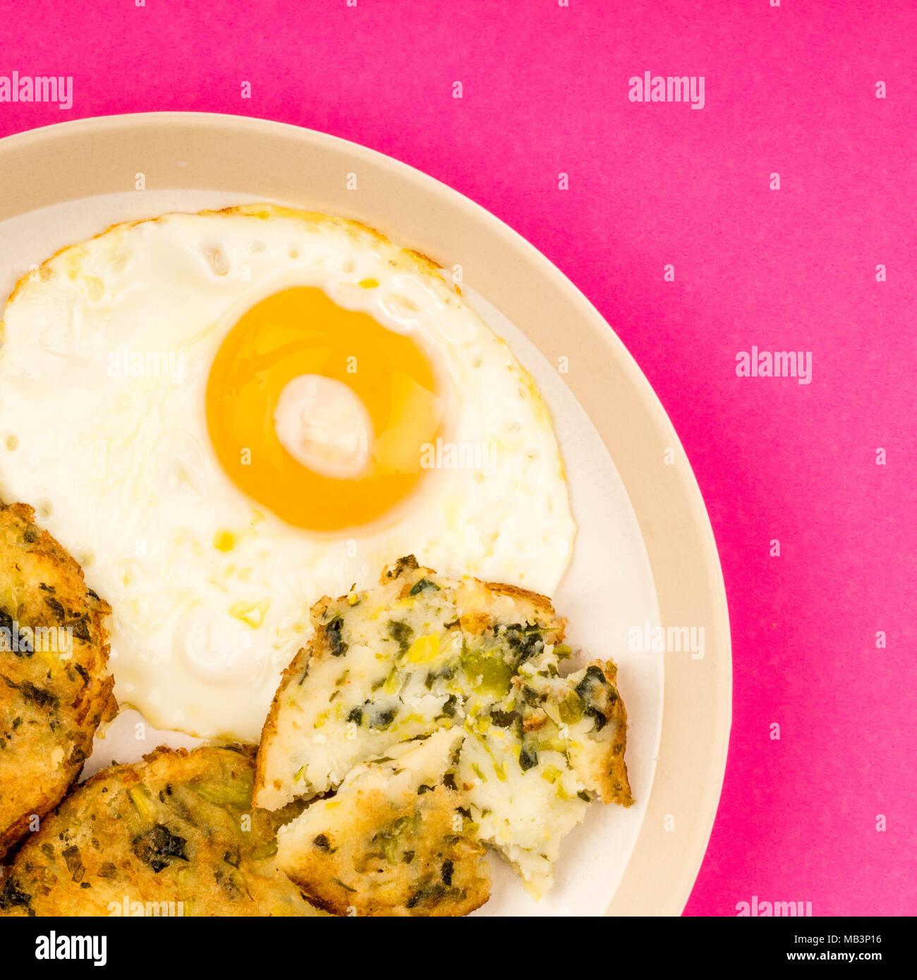 Spiegeleier auf einem Teller mit Bubble und Squeak Frikadellen Essen Stockbild