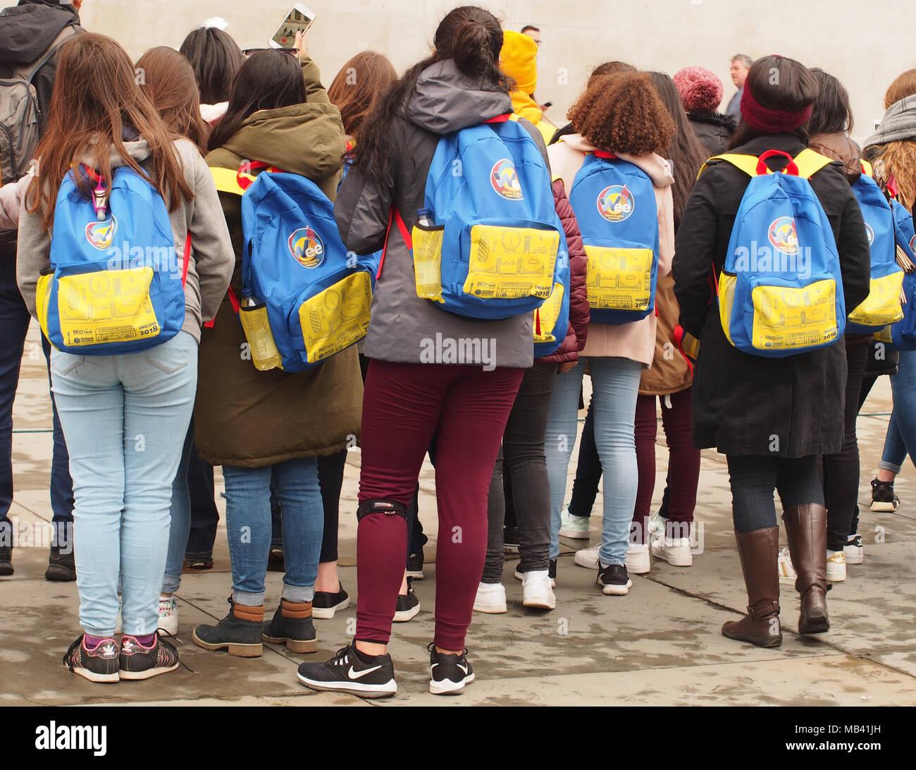 Ein Blick auf die Rücken von einer Gruppe von Studenten, die London besichtigen auf dem Trafalgar Square, einer der Animateure, alle, die identischen Rucksäcke Stockbild