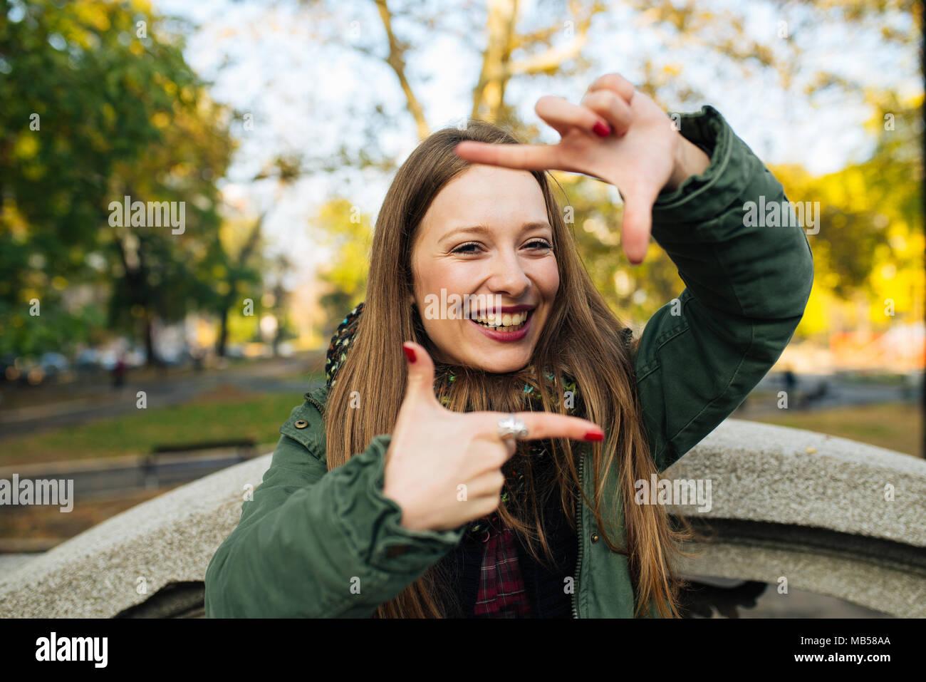 Attraktive junge Frau im grünen Mantel, finger Rahmen im Freien ...