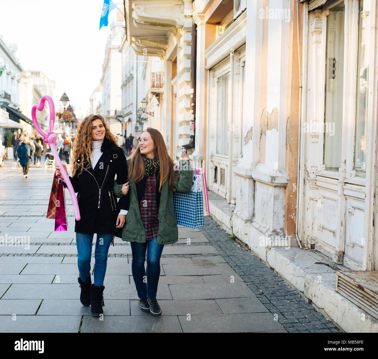 Zwei attraktive junge Frauen ist mit Einkaufsmöglichkeiten zufrieden und auf der Straße Stockbild