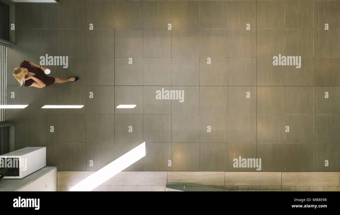 Blick von oben auf eine Geschäftsfrau eingabe Büro Flur mit Kaffee und Gespräch am Handy. Blick von oben auf die geschäftsfrau im Bürogebäude Lobby. Stockfoto