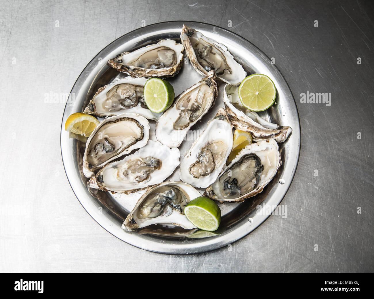 Mehrere geöffnete Austern mit Zitrone und Limone. Stockbild