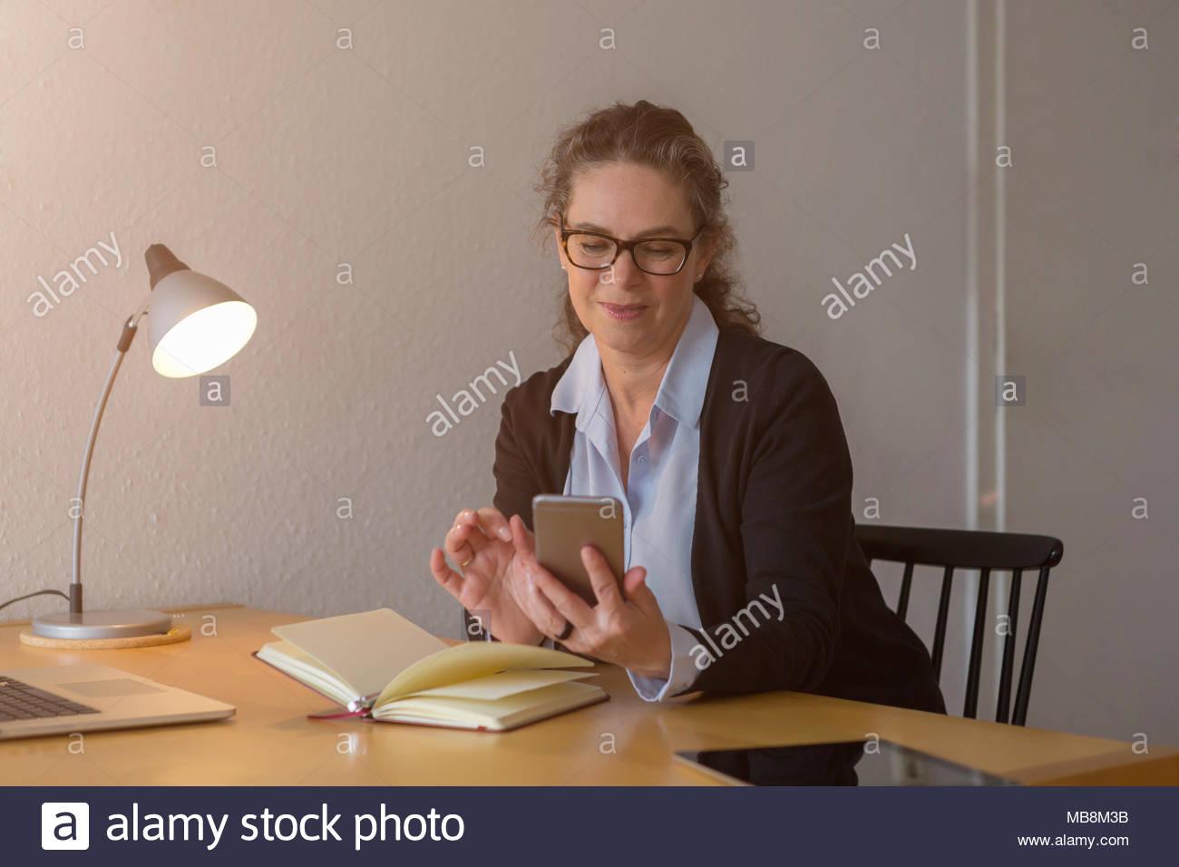 Geschäftsfrau Lesen einer Nachricht auf ihr Handy Stockbild