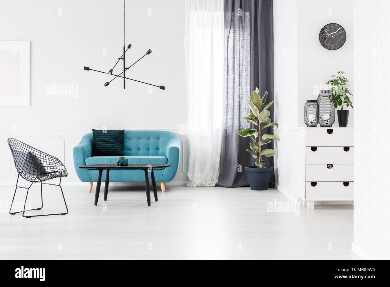 Sessel neben Schwarz und Blau Sofa gegen weiße Wand im Wohnzimmer ...