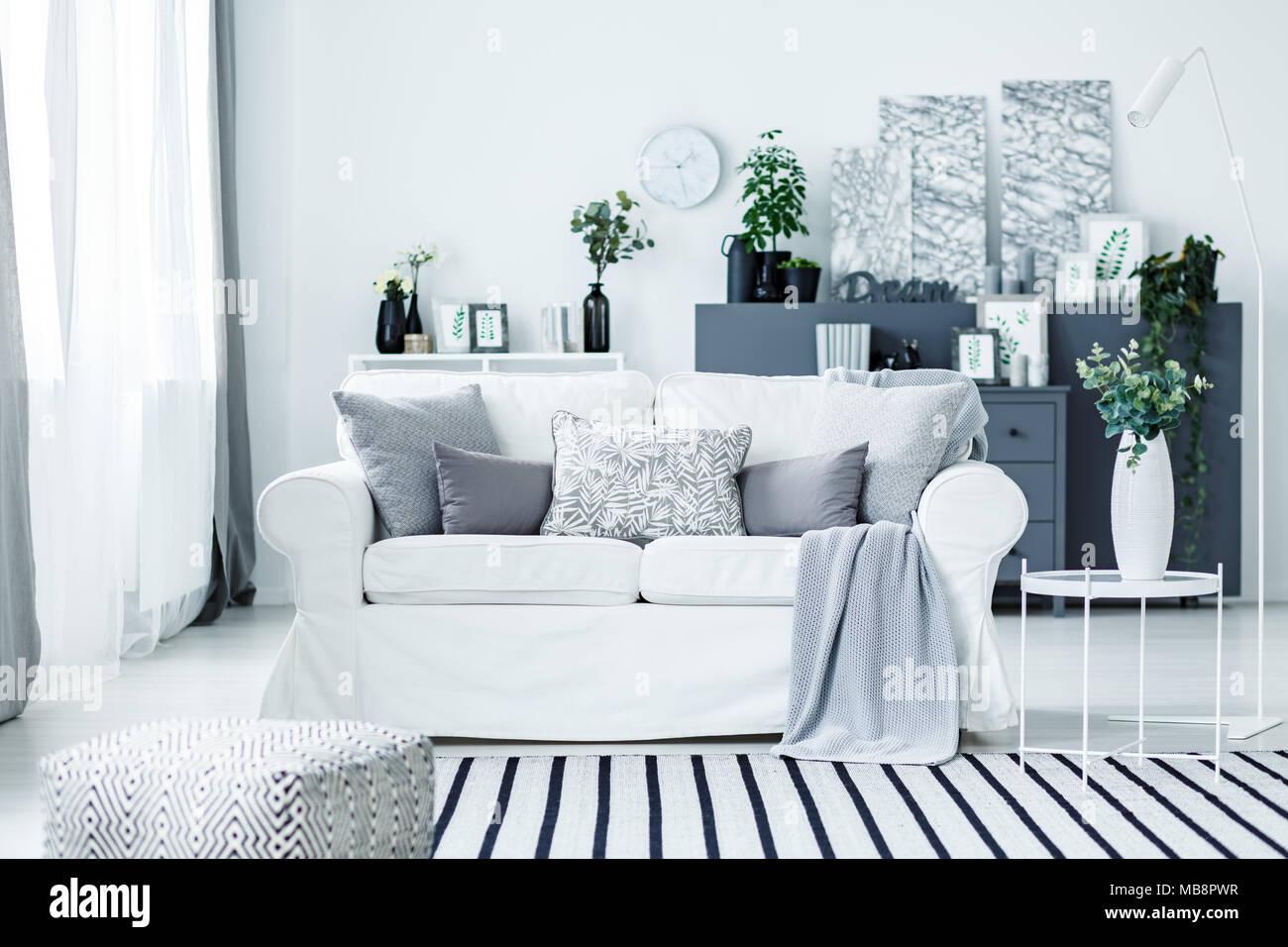 Gemütliche Weiß Sofa Und Einem Gestreiften Teppich In Ein Stilvolles, Modernes  Wohnzimmer Interieur Mit Grauen Möbeln Und Dekorationen