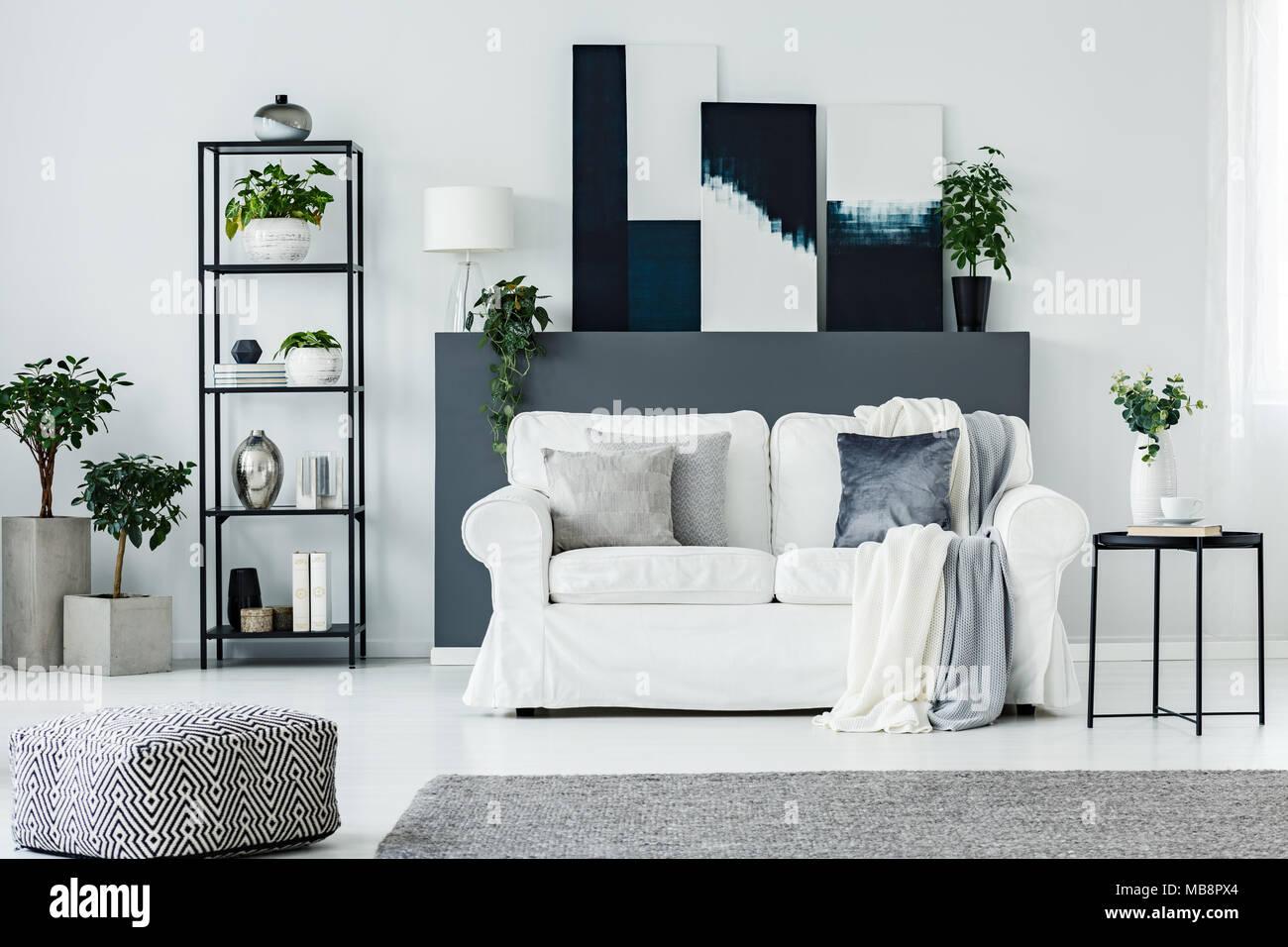 Bequemes Sofa Durch Eine Graue Wand Mit Abstrakten Gemälden In Einem  Designer Wohnzimmer Einrichtung Mit Pflanzen In Stilvollen Konkrete  Pflanzmaschinen