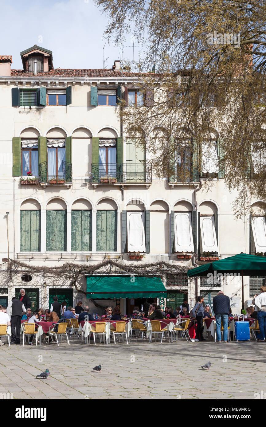 Campo San Polo, San Polo, Venedig, Venetien, Italien im Frühjahr bei Einheimischen und Touristen essen im Freien an Tischen, die in der Pizzeria Bar Cico Stockbild