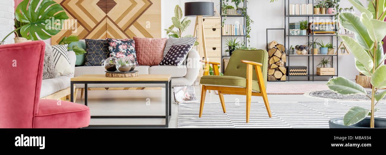 Grün Holz Sessel neben Sofa mit gemusterten Kissen in Wohnzimmer ...