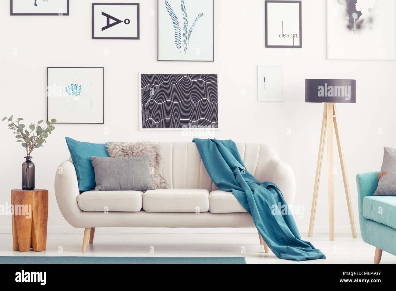 Blaue Decke Auf Beige Sofa Zwischen Hölzernen Stuhl Und Lampe Im Wohnzimmer  Mit Galerie